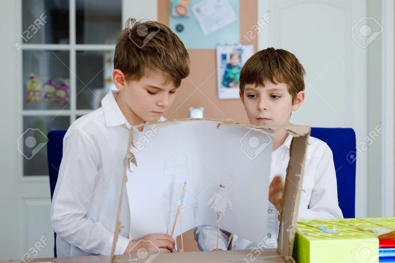 Two little school kids boy making paper doll theatre. Happy children and friends creating figures and performing stage play during quarantine time at home. Active creative siblings staying at home. - 144704385