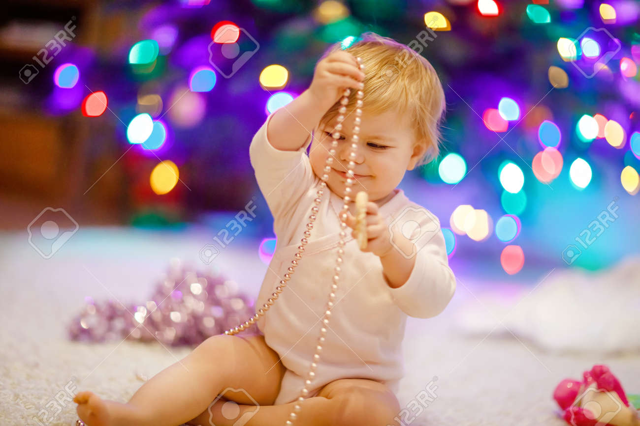 Adorable baby girl holding colorful lights garland in cute hands. Little child in festive clothes decorating Christmas tree with family. First celebration of traditional holiday called Weihnachten - 154207811