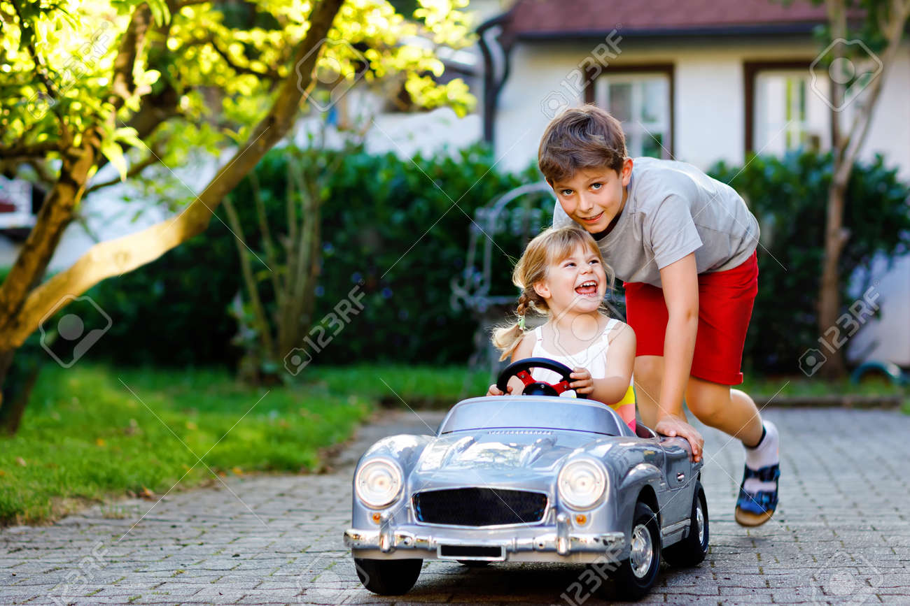 Two happy children playing with big old toy car in summer garden, outdoors. Kid boy pushing and driving car with little toddler girl, cute sister inside. Laughing and smiling kids. Lovely family - 154035905