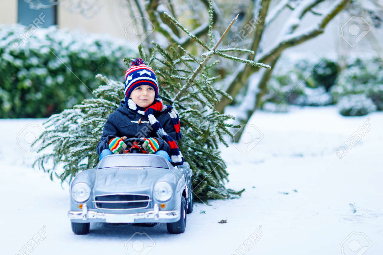Funny little smiling kid boy driving toy car with Christmas tree. - 156299477