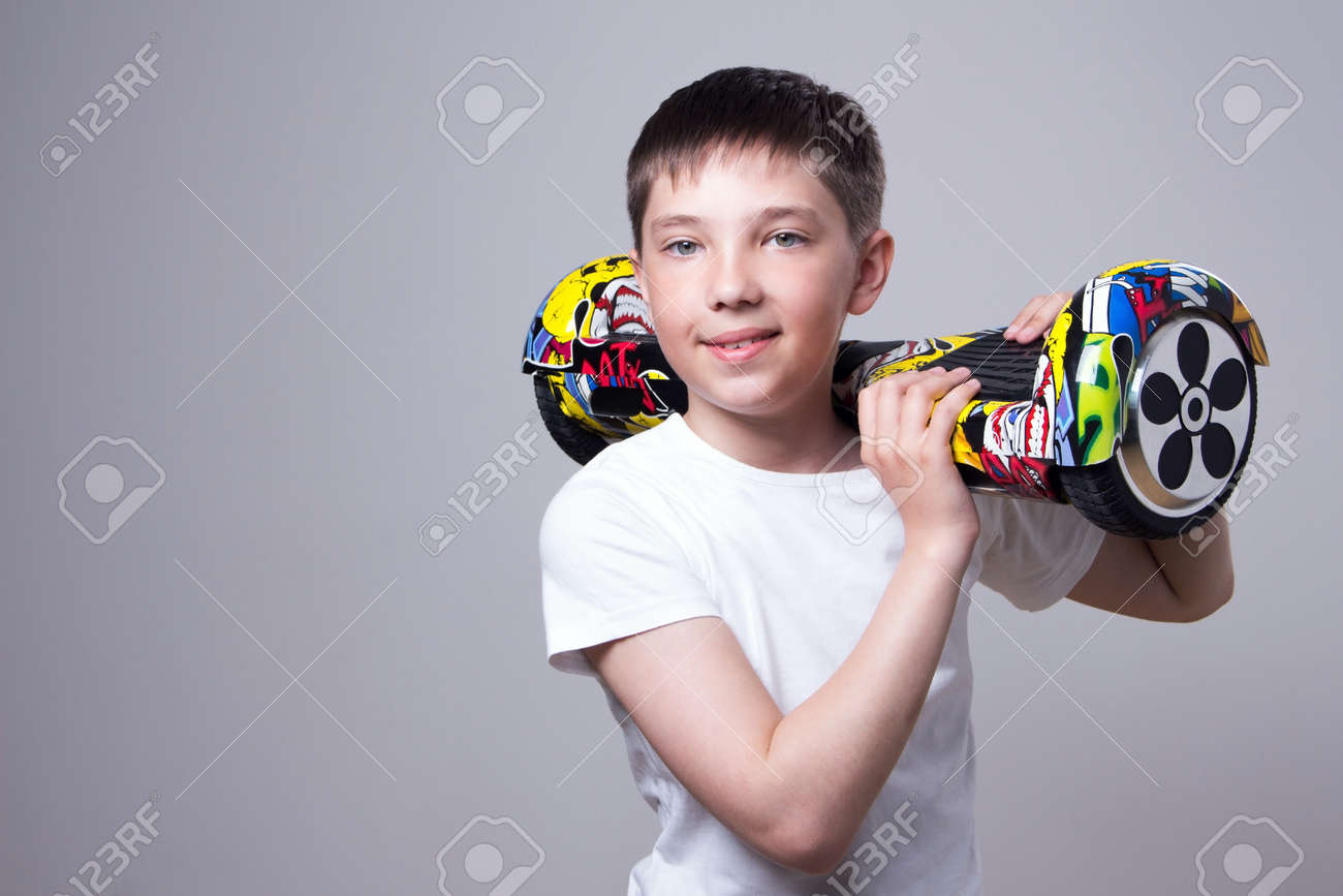 A happy European boy in a white T-shirt holds a popular hoverboard in the eb7e19deb2a