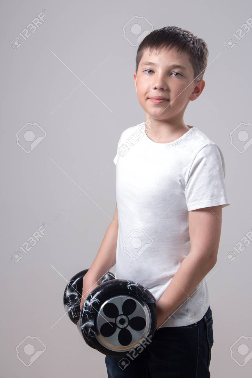 A Cute Teenager In A White T-shirt Is Holding A Black Self-balancing ... 3563f644b19