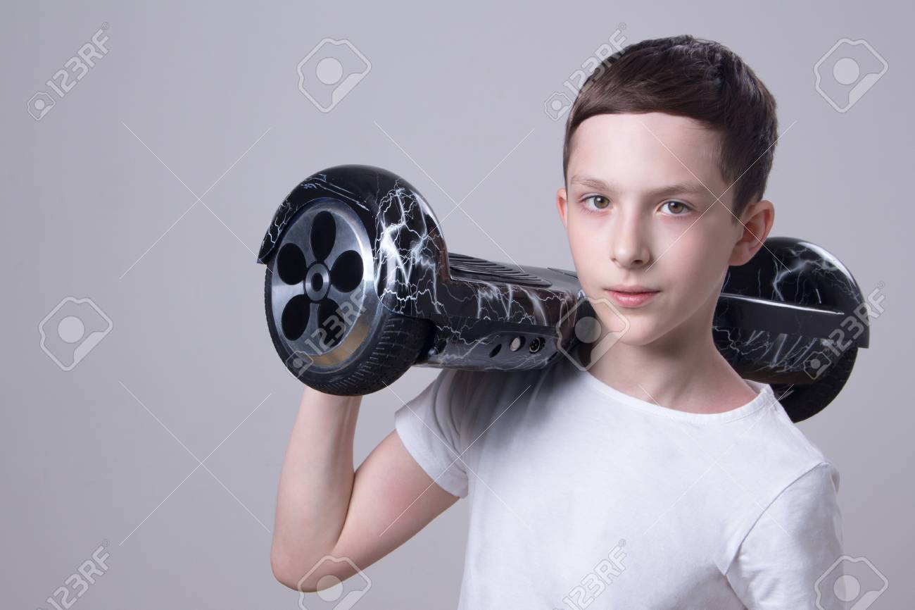 Stock Photo - The European guy in a white T-shirt holds on his right  shoulder a super popular black color with a lightning hoverboard. 7a5f43cf57f