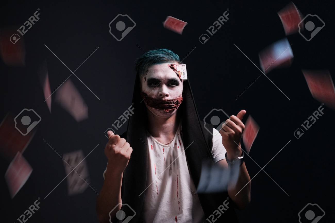 halloween makeup. the guy in the image of joker threw cards stock