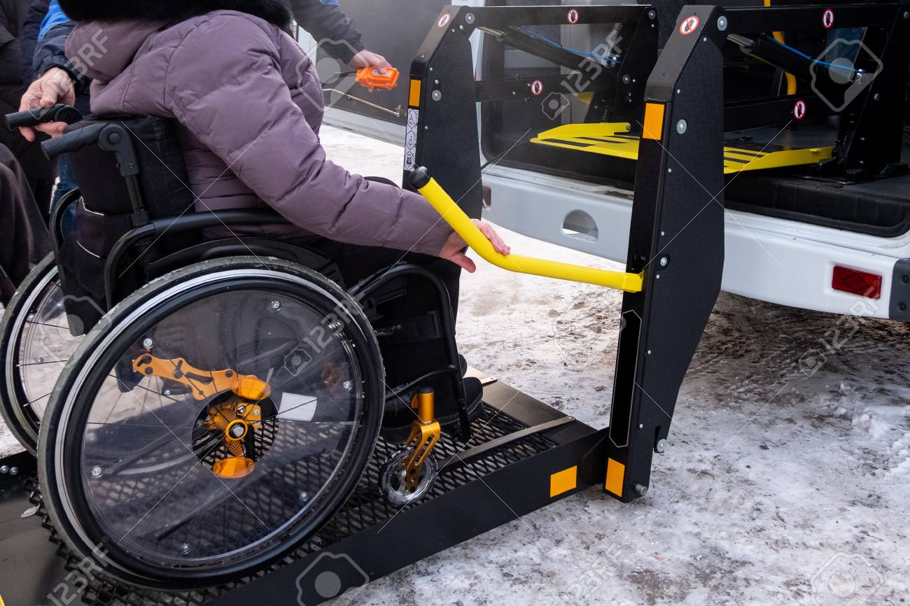 A man presses a button on the control panel to pick up a woman in a wheelchair in a taxi for the disabled. Black lift specialized vehicle for people with disabilities. Yellow handrail. Winter time. - 114939754