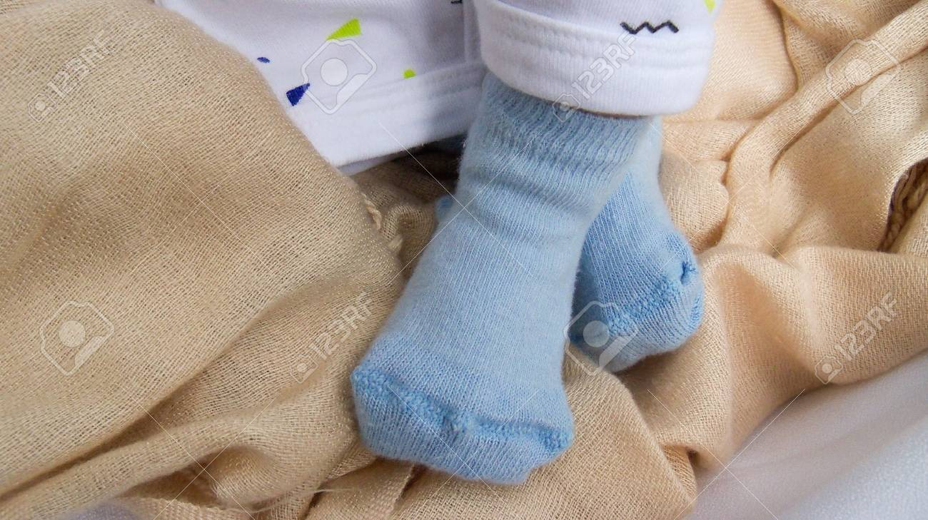 Newborn Baby Feet In Blue Socks Closeup Stock Photo Picture And