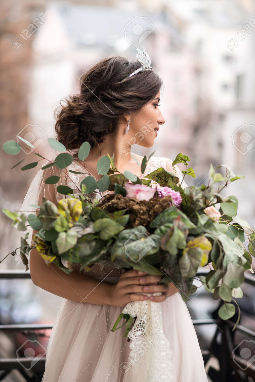 bride with a bouquet of flowers on the balcony - 70804679