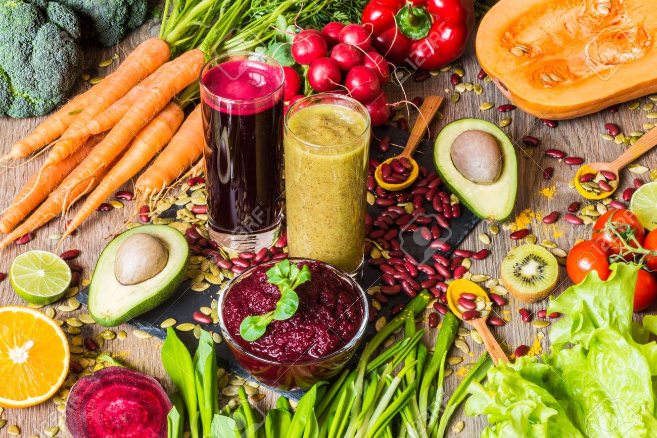 Healthy vegan food. Fresh vegetables on wooden background. Detox diet. Different colorful fresh juices - 75459808
