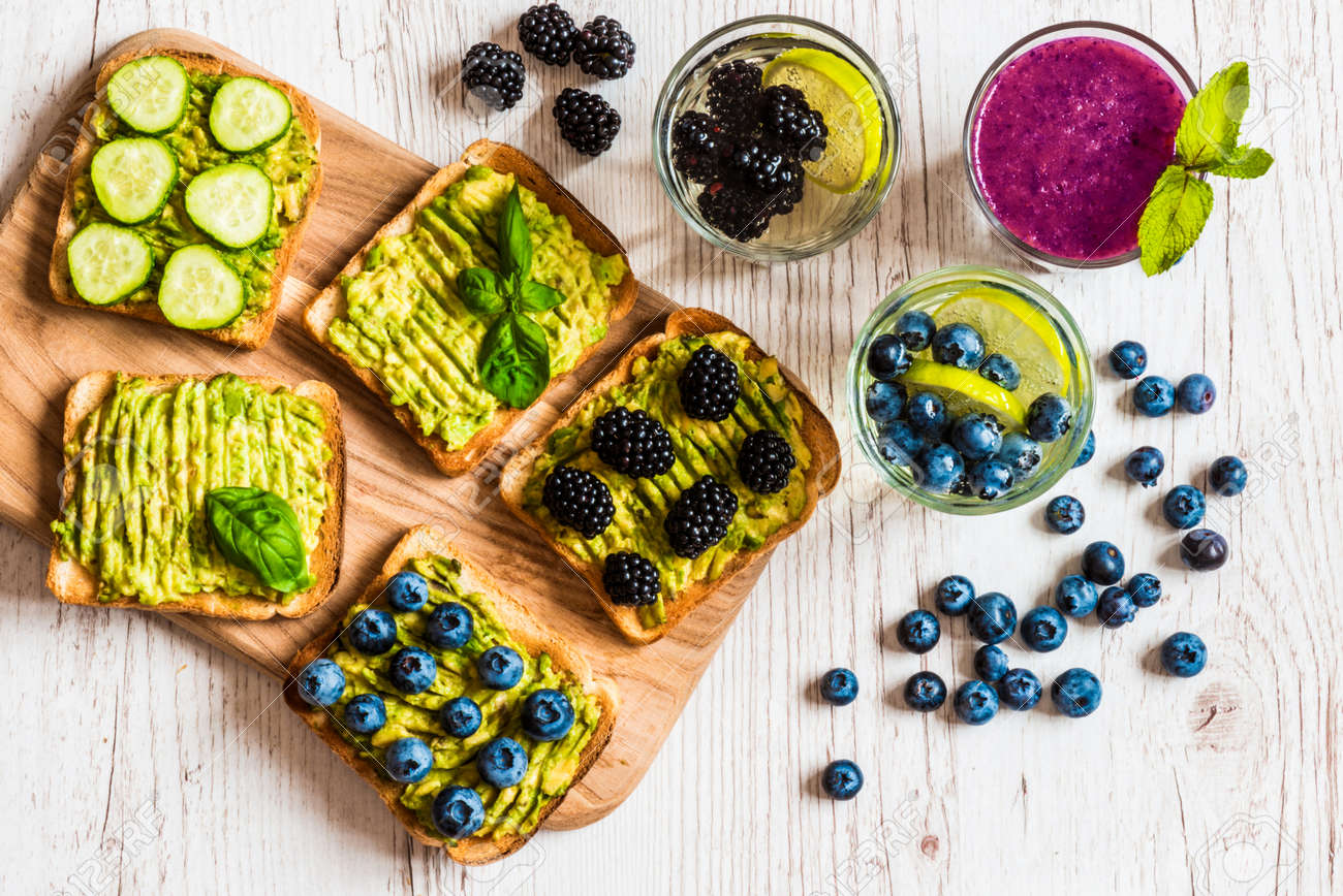 Set of vegetarian toast sandwiches with avocado and drinks. Variety of healthy food and drinks on white wooden background - 82330702