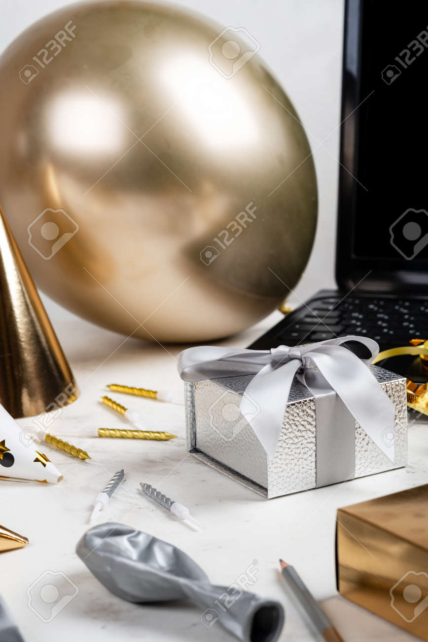 Online celebration concept. Silver festive box and laptop Balloon Other accessories on the white table - 167848324