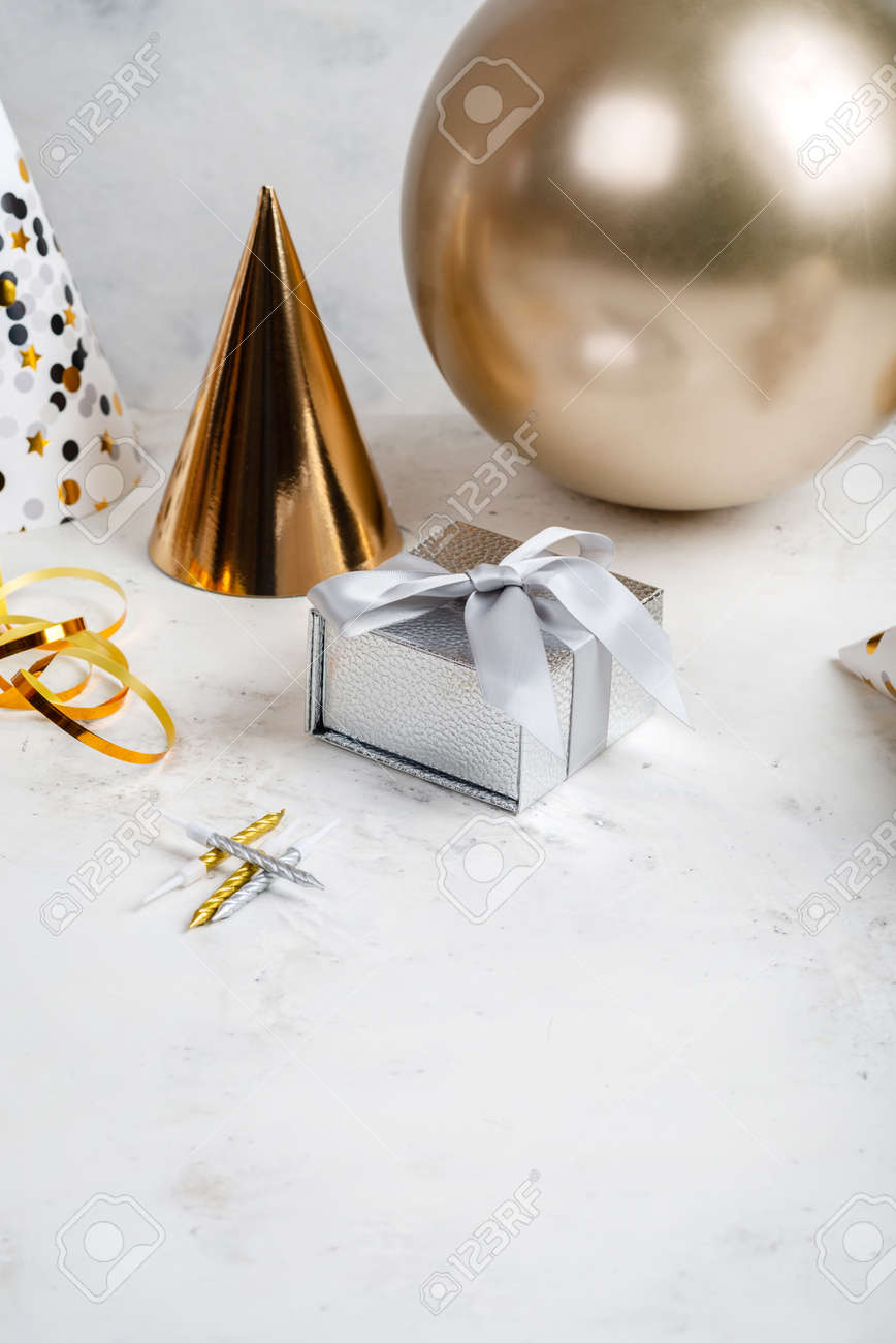 Festive composition Silver gifts box Golden party hat and balloon on white background with place for text - 167848425