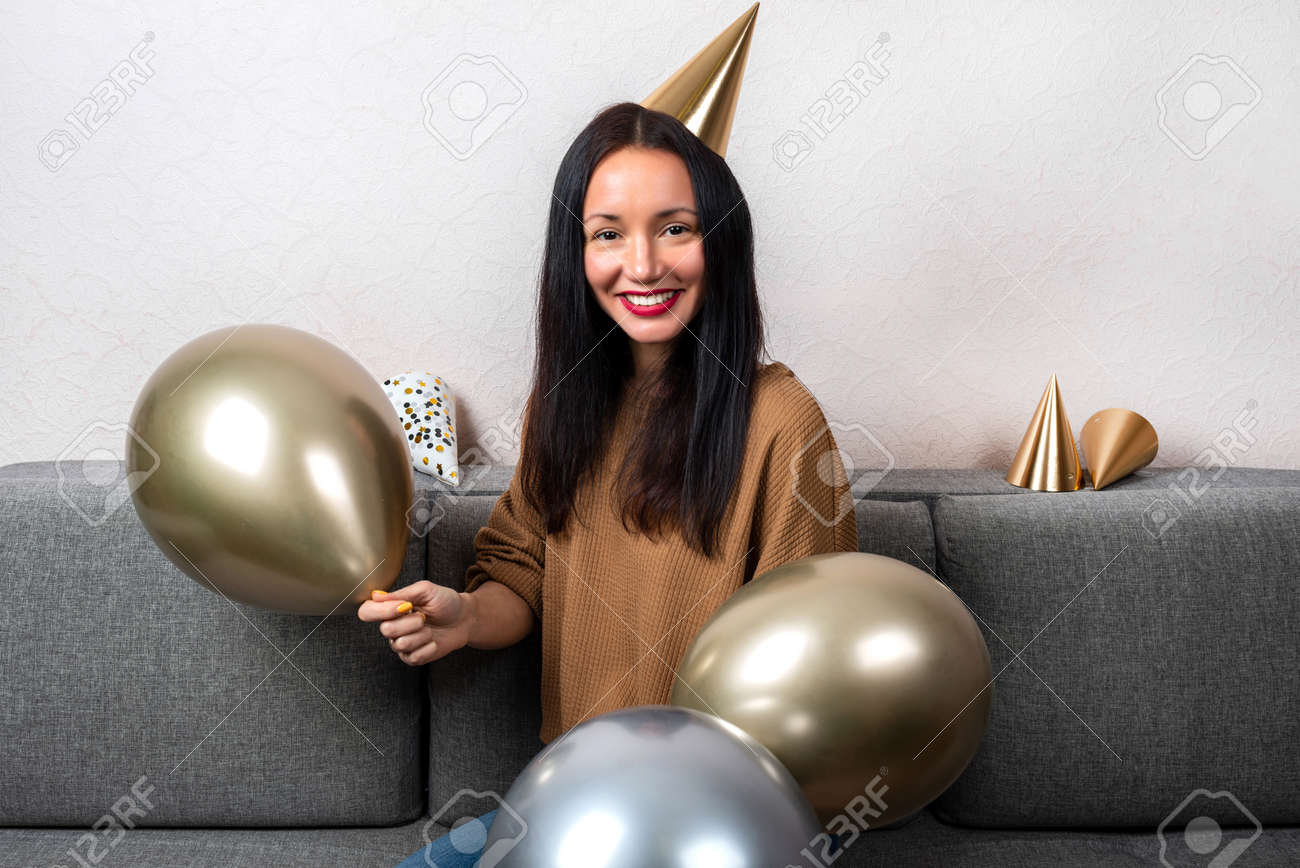 Smiling young woman wearing in party hat with balloons are celebrating birthday at home - 167848427