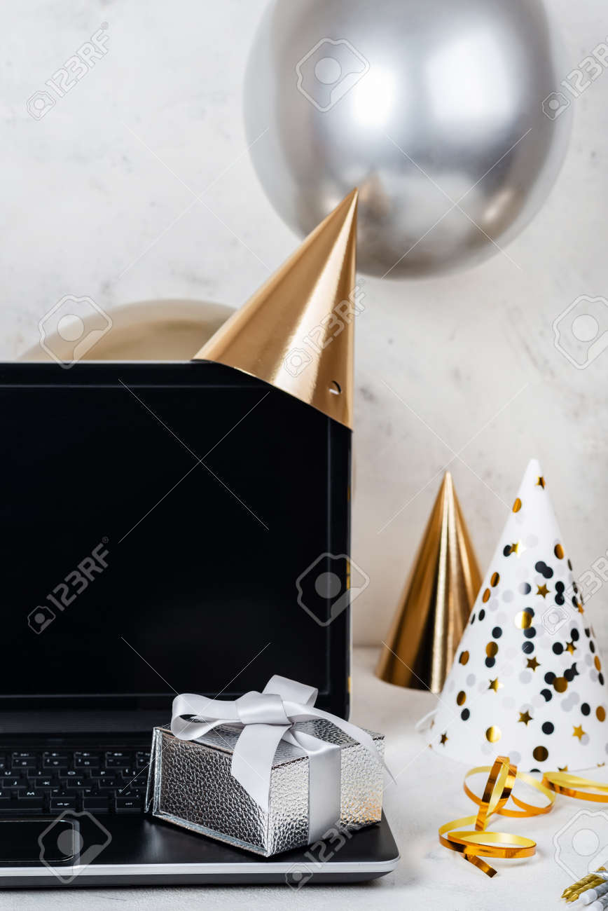 Silver festive box and blank screen laptop with party hats and balloons. - 167848535