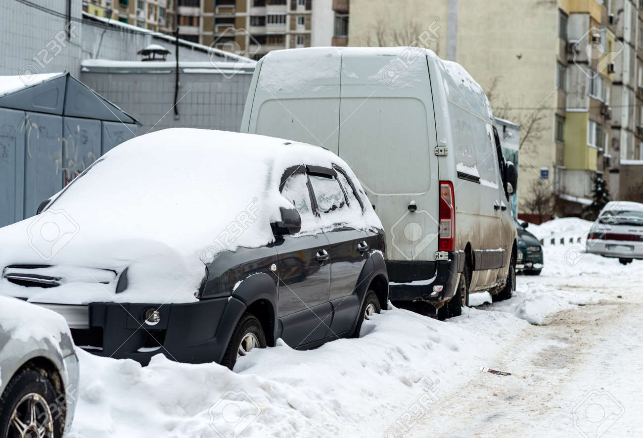 Cars stand in the yard covered with snow - 163754394