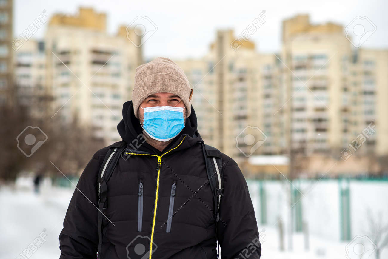 a man walking down the street wearing a protective mask middle plan - 164446631