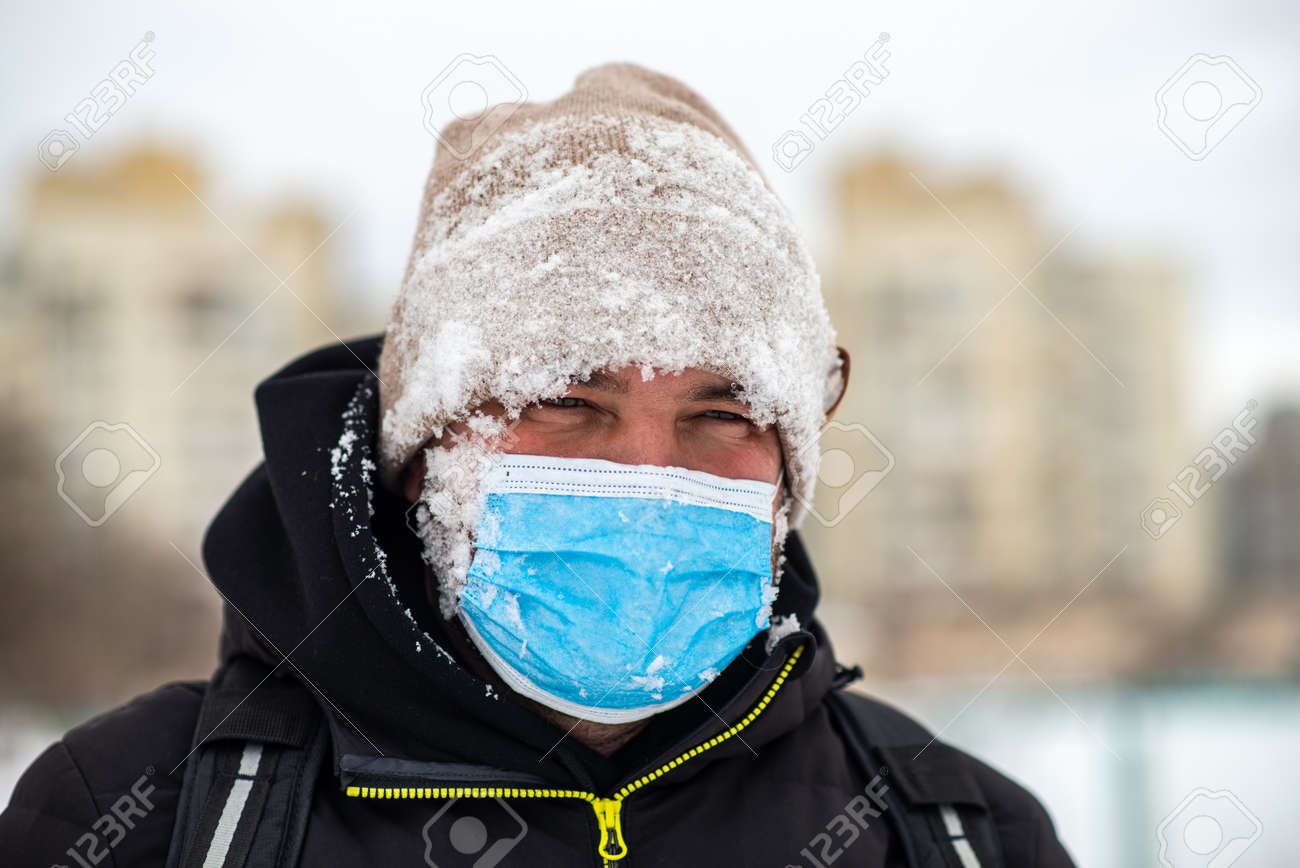 a man walking down the street wearing a protective mask close-up - 164446632