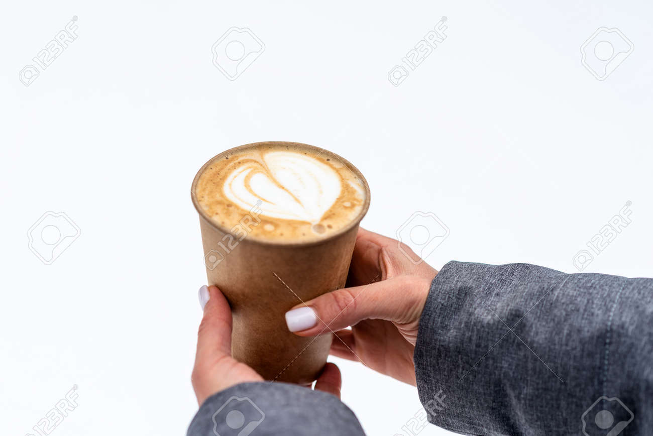Girl holding a glass of cappuccino over the snow close-up. - 163917936