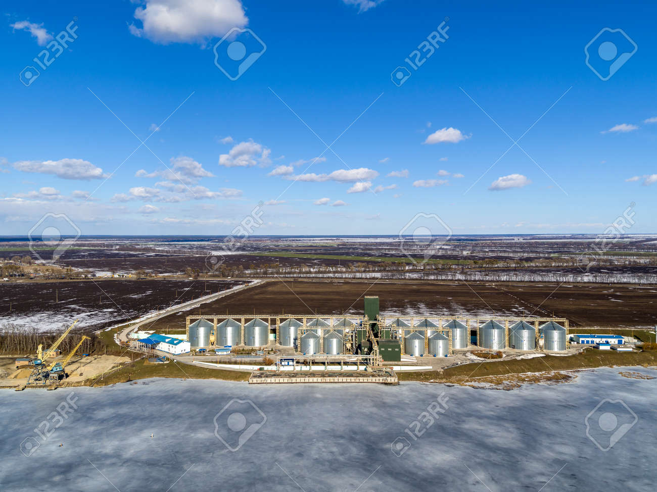 Agro-processing plant for processing and silos for drying cleaning and storage of agricultural products, flour, cereals and grain with beautiful clouds and frozen river in winter - 165561753