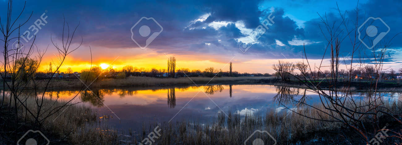 Beautiful golden sunset with reflection of clouds in the lake in the village panorama - 170818672