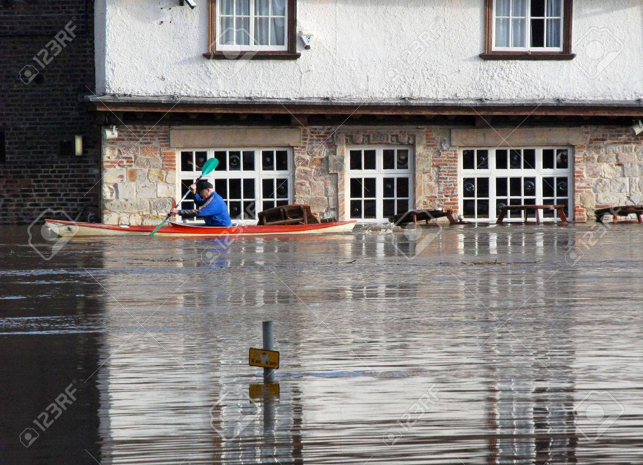 Canoeist paddles past flooded pub. River Ouse, York, North Yorkshire, UK. Stock Photo - 2482961