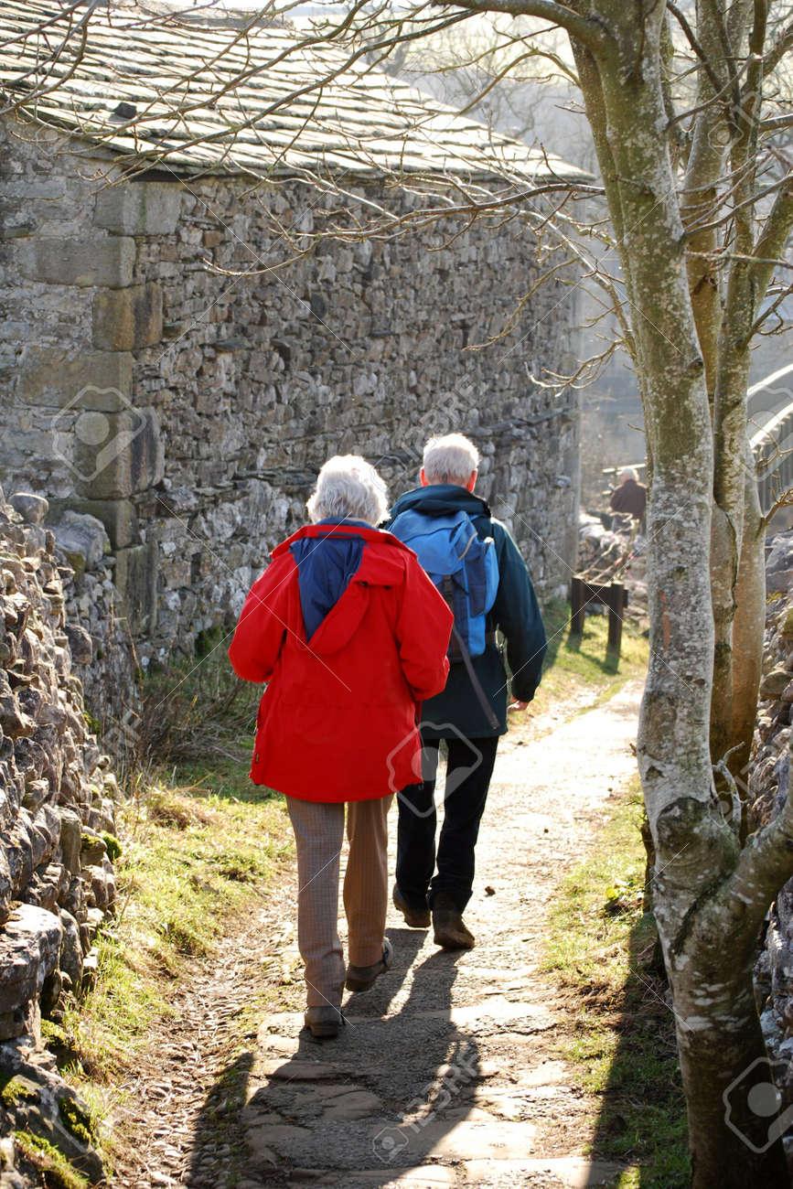 Elderly couple walk down country lan in Grassinton, Yorkshire, UK Stock Photo - 3243065