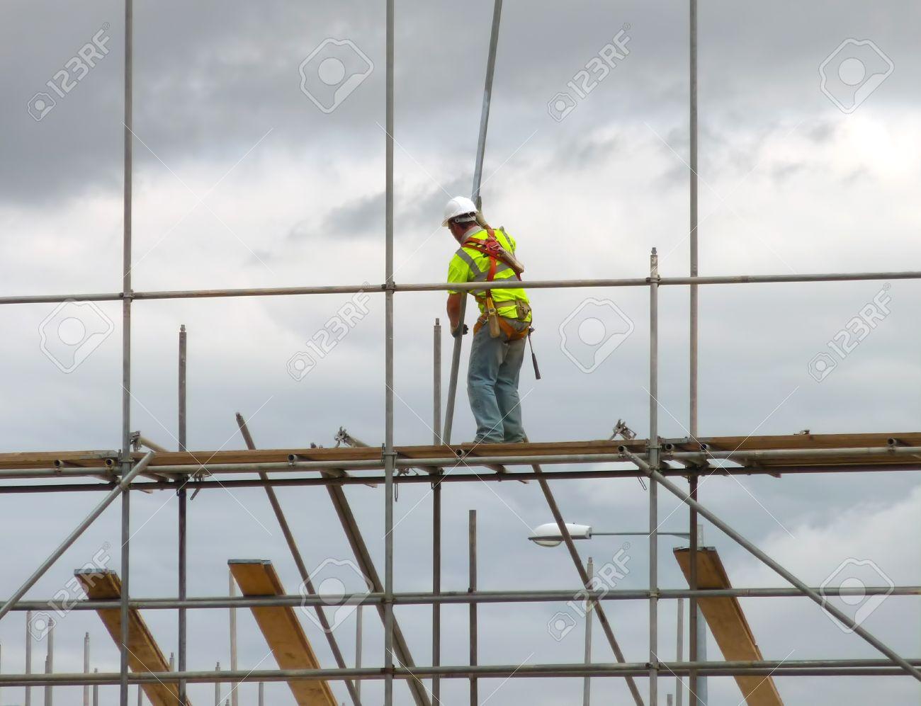 closeup of construction worker assembling scaffold on building closeup of construction worker assembling scaffold on building site stock photo 7833522