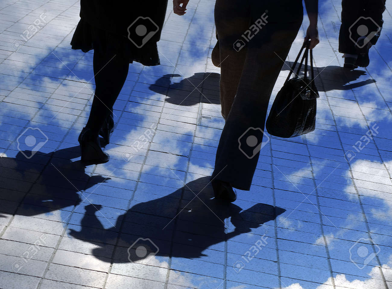 Silhouetted pedestrians in city center overlaid with clouds Stock Photo - 8392729