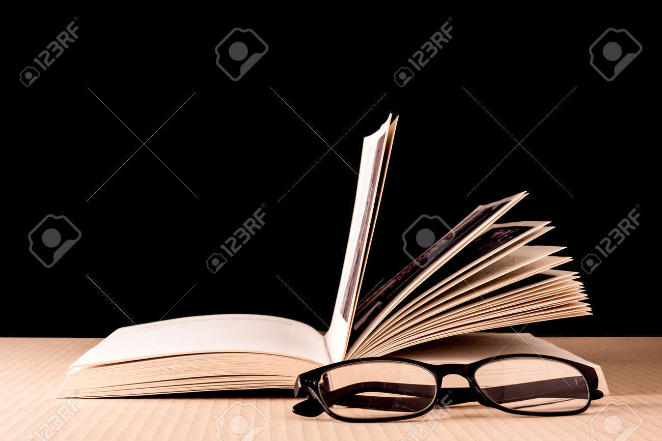 Book and eyeglasses on wooden table, Black background - 72432966