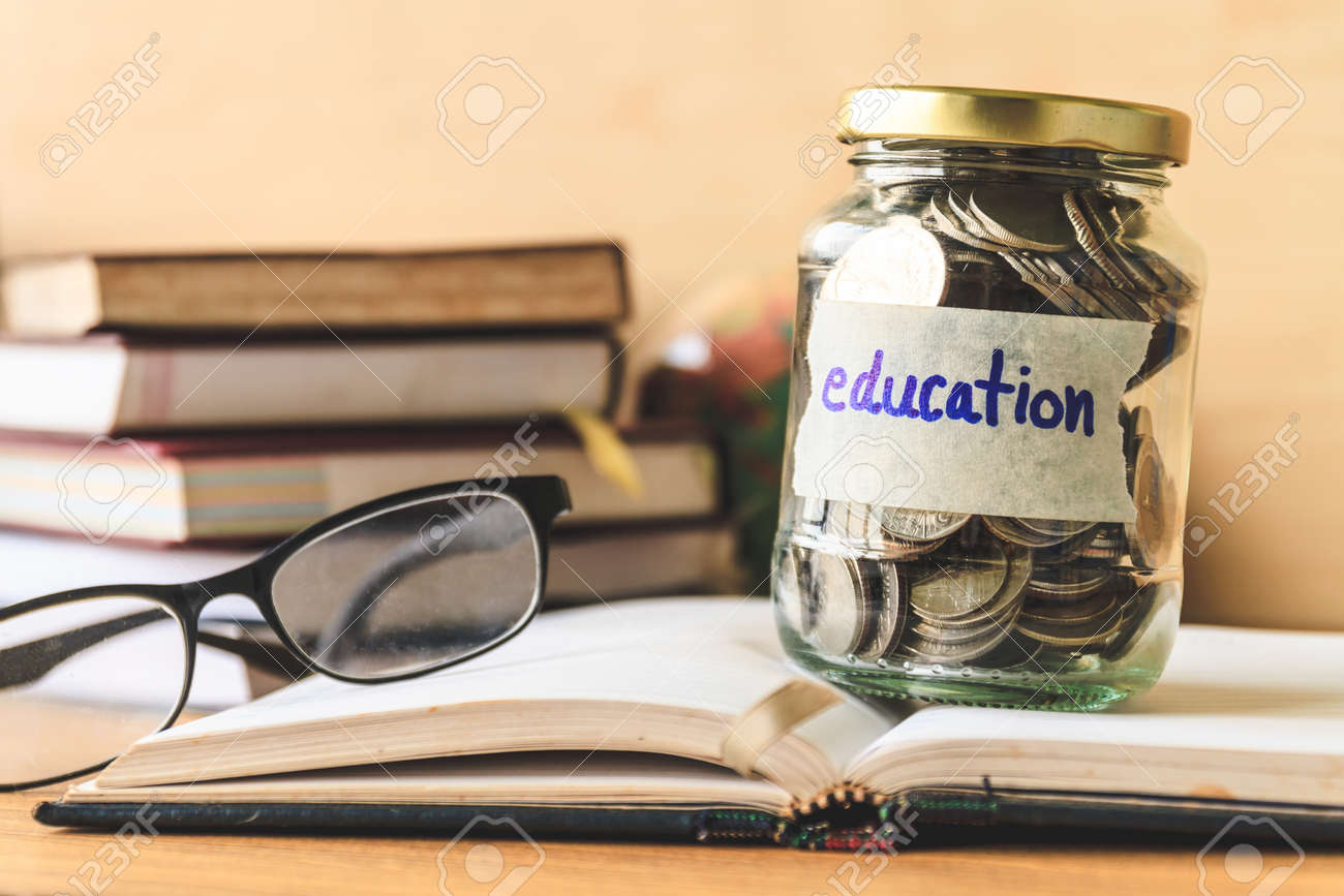 Coins in glass jar with education label, books,glasses and globe on wooden table. Financial concept. - 75830394