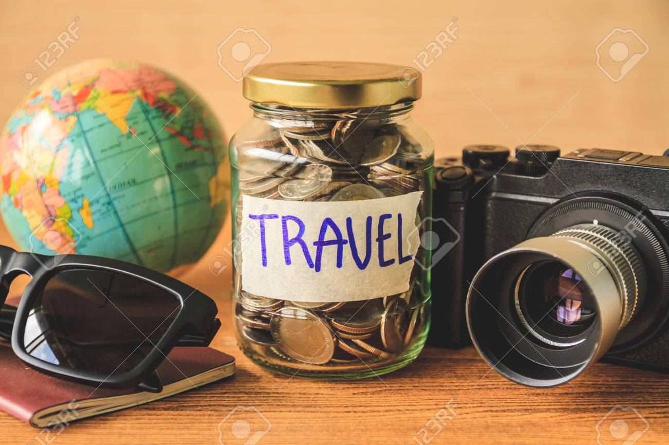 Coins in glass jar with accessories of traveler on wooden table. Saving money for travel concept - 75830392