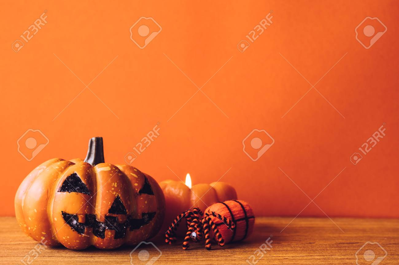 Halloween Pumpkins With Candlelight On An Orange Color Background. Free  Space For Text Stock Photo