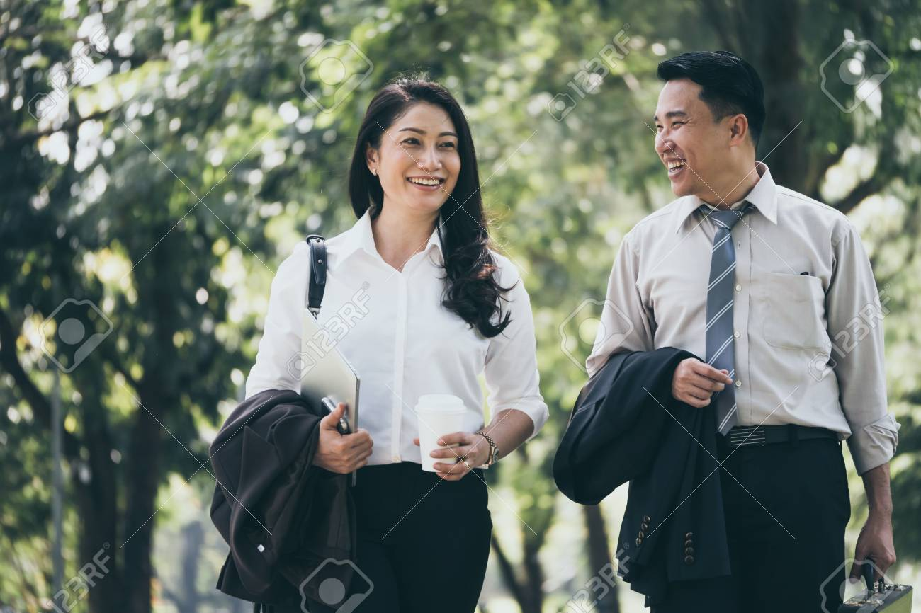 Happy Asian business man and woman walking and talking in the public park after finish work. - 92600961