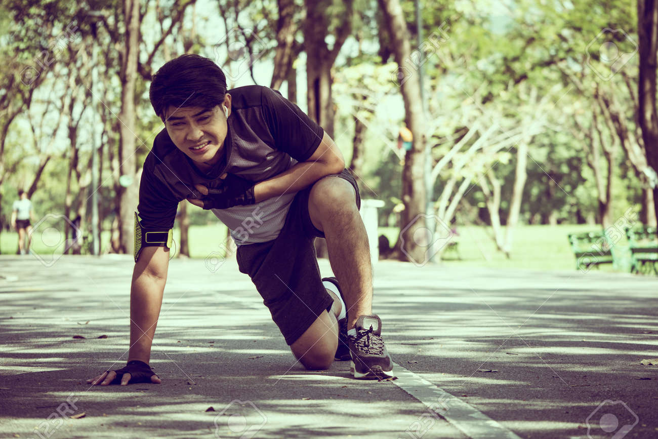 An Asian man has a heart pain while exercising in a park. - 94426271