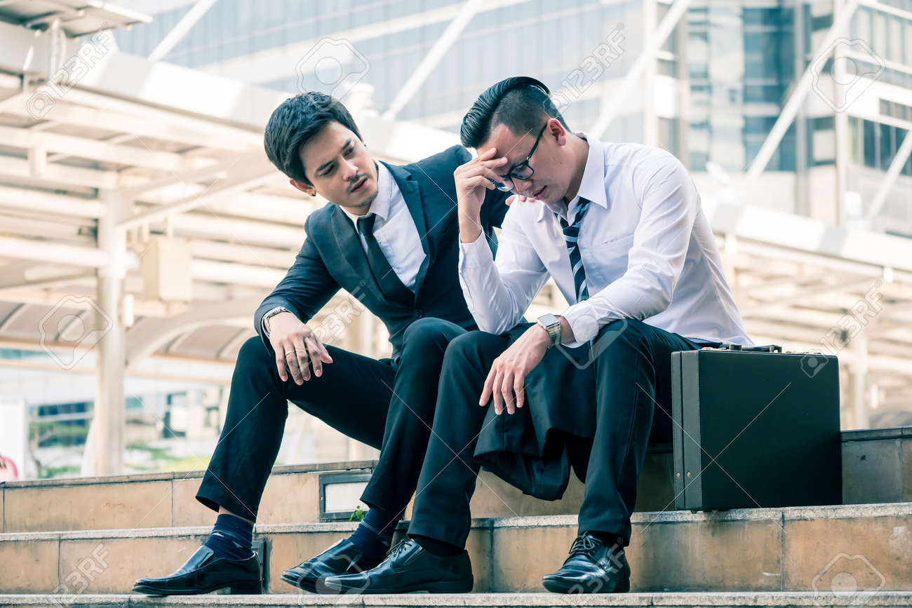 Frustrated Asian young business man sitting outdoor office after he had failed in new project, his colleagues tried to reassure his. - 100743627