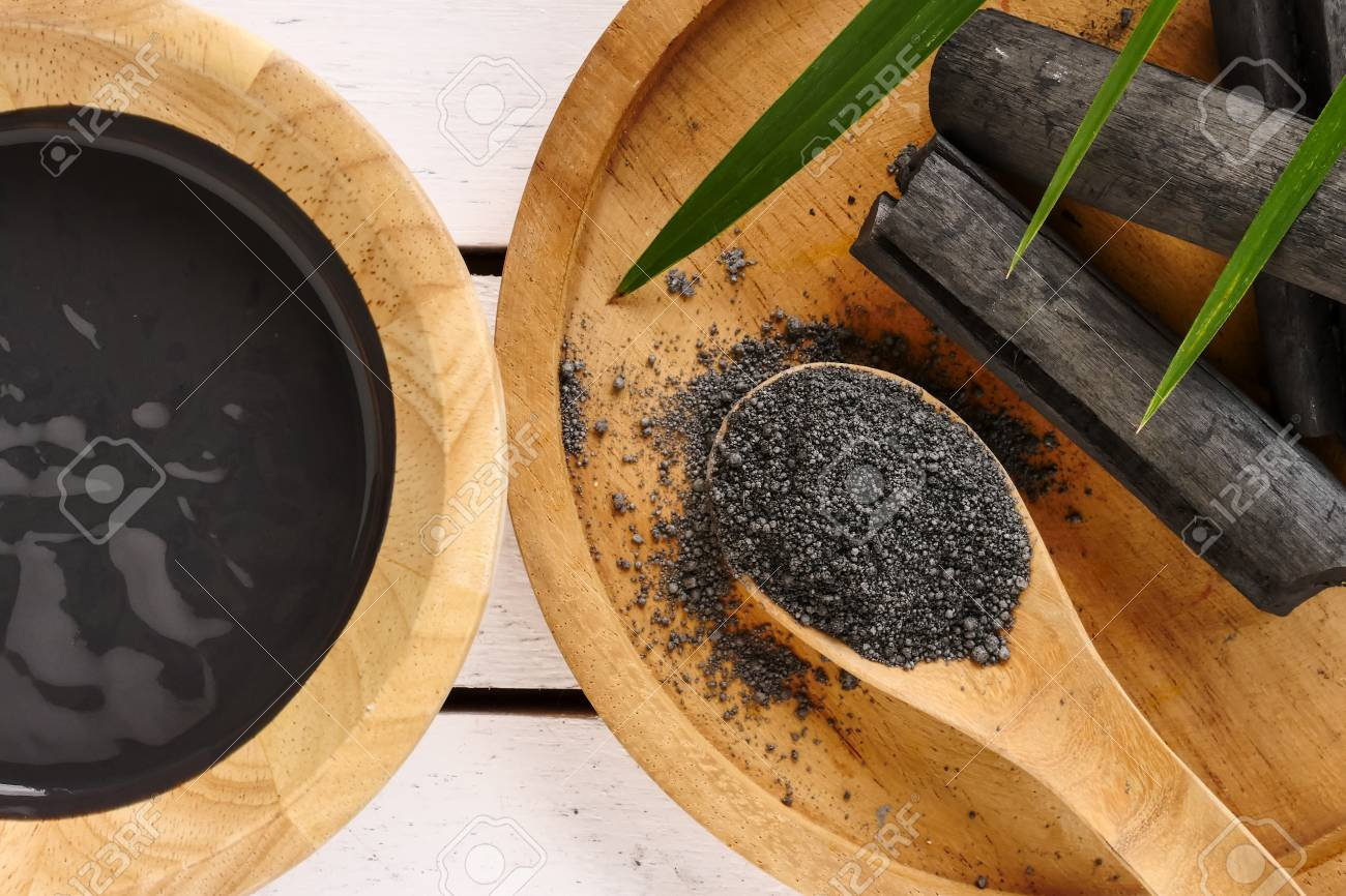Facial mask and scrub by activated charcoal powder on wooden table - 105102522