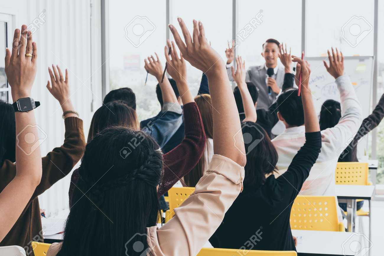 Audience raising hands up while businessman is speaking in training at the office. - 109206270