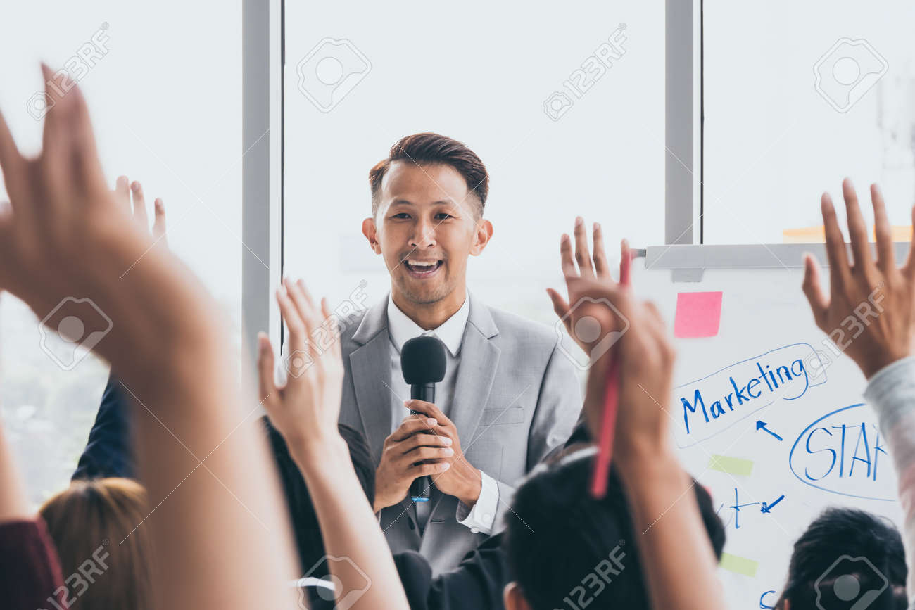Audience raising hands up while businessman is speaking in training at the office. - 109816548
