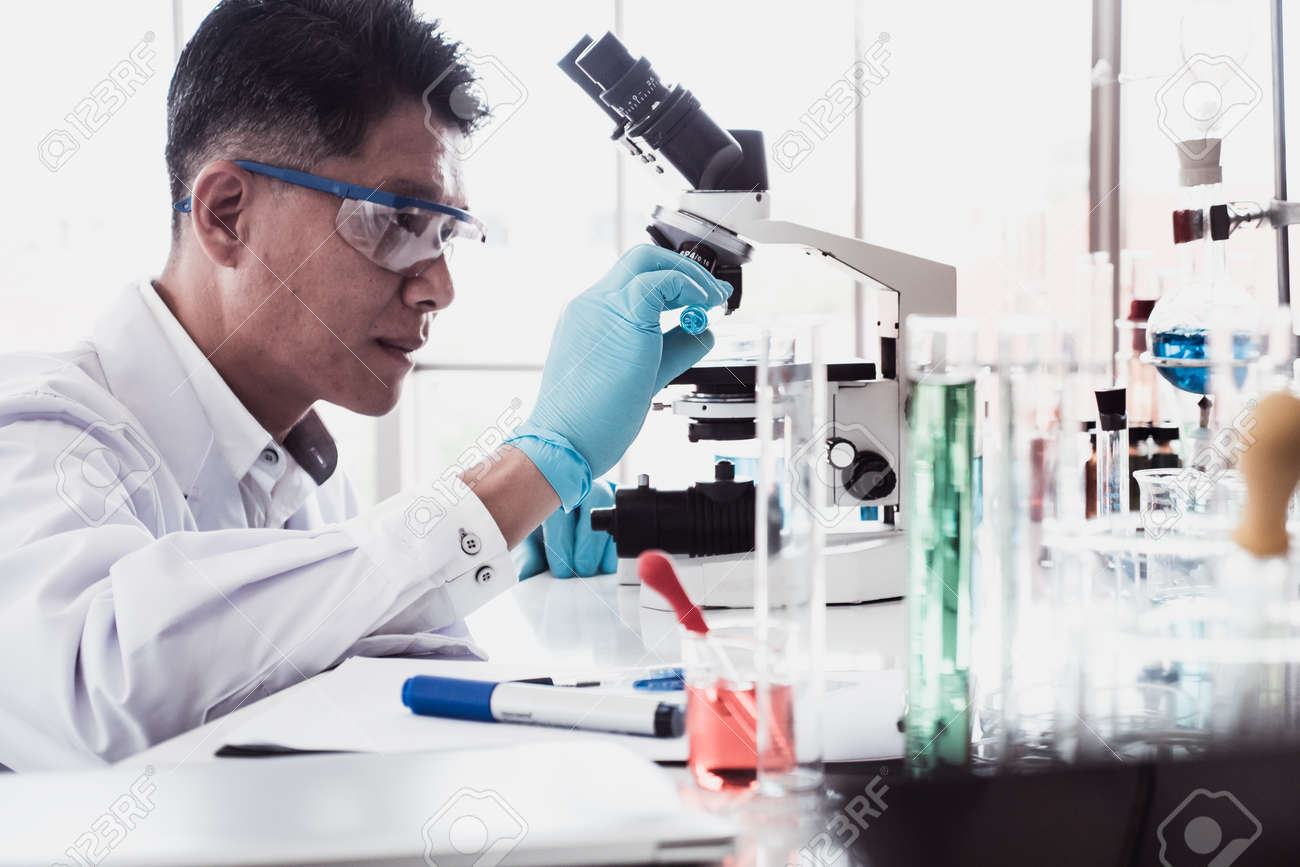 Scientist doing some research and looking through a microscope in a laboratory - 116546980