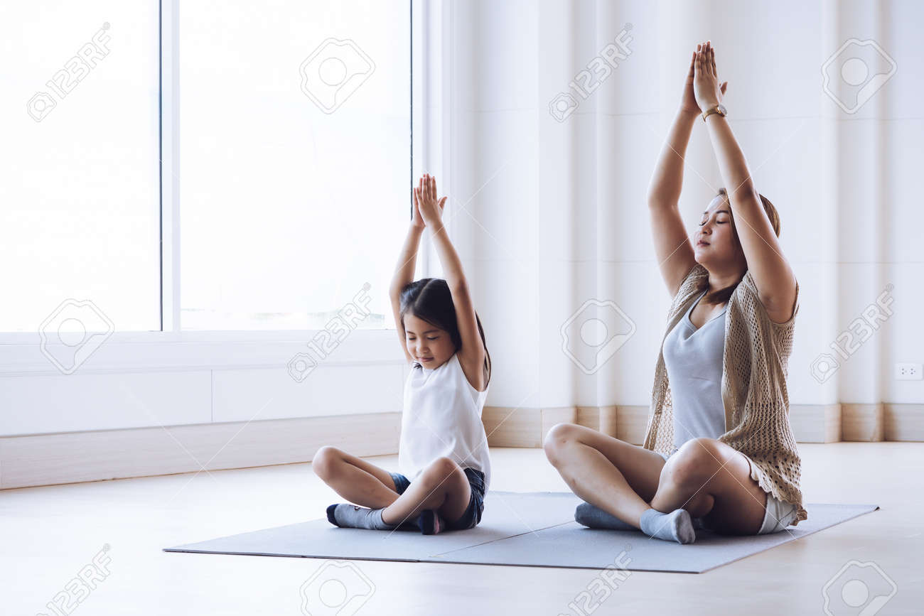 Asian mother and her kid daughter doing stretching exercise at home - 128695056
