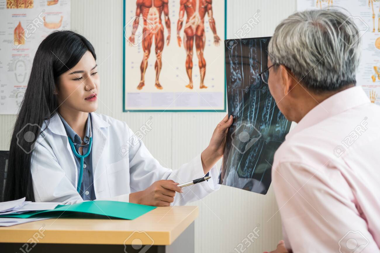 Expert doctor examining and explaining x-ray film to elderly patient in medical office - 128927471