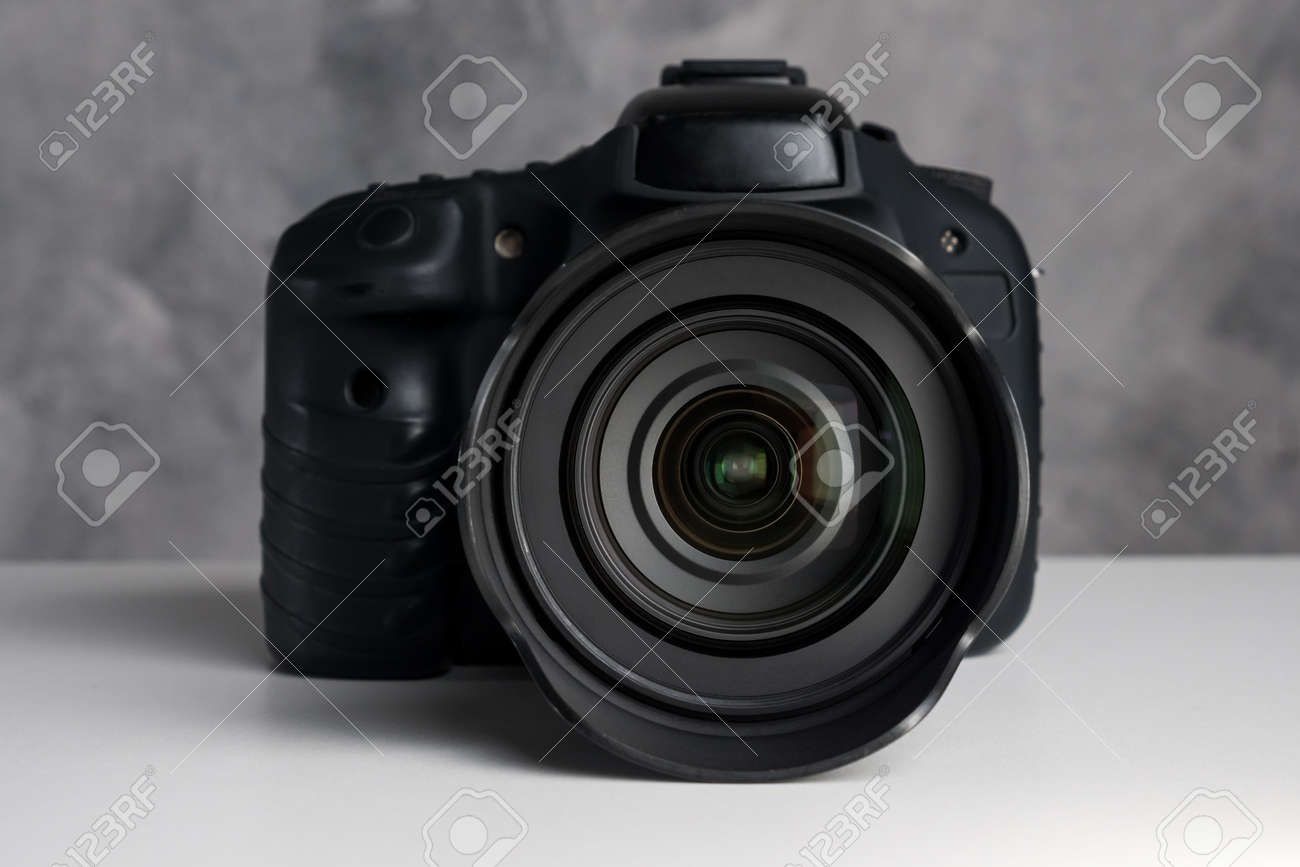 Black digital camera on a table with grunge background. - 143663580