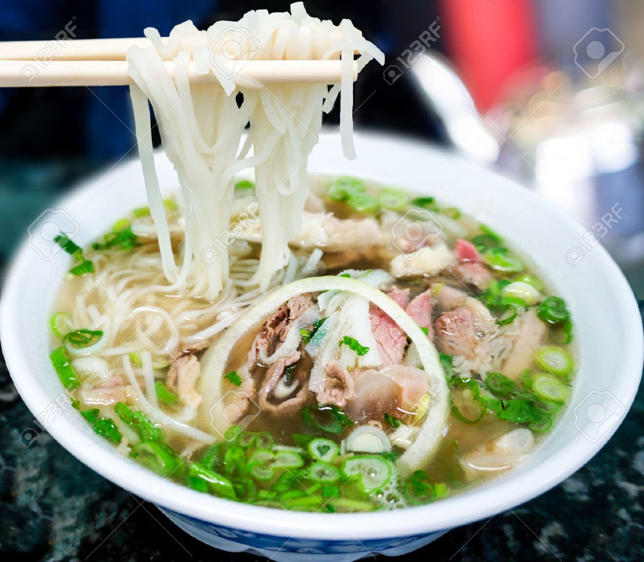 Bowl of Vietnamese pho noodle soup with rare beef, tendon, tripe