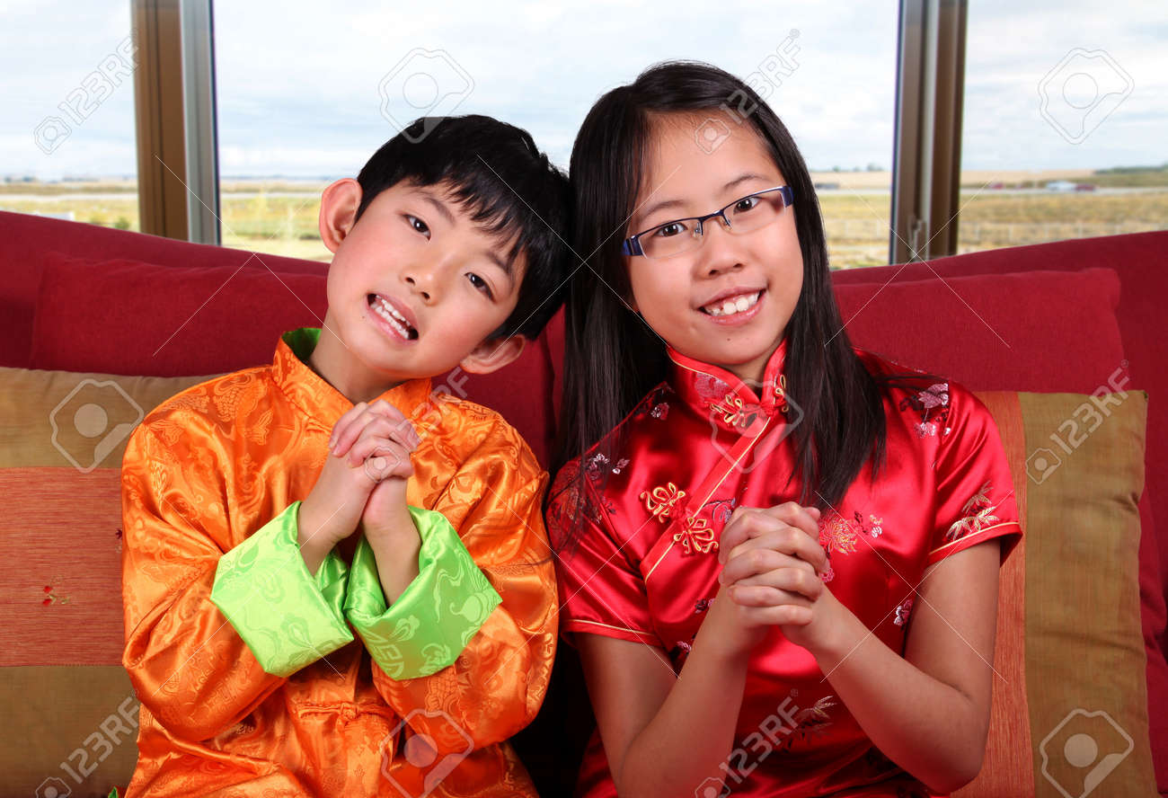 two cute children in traditional chinese new year outfits making