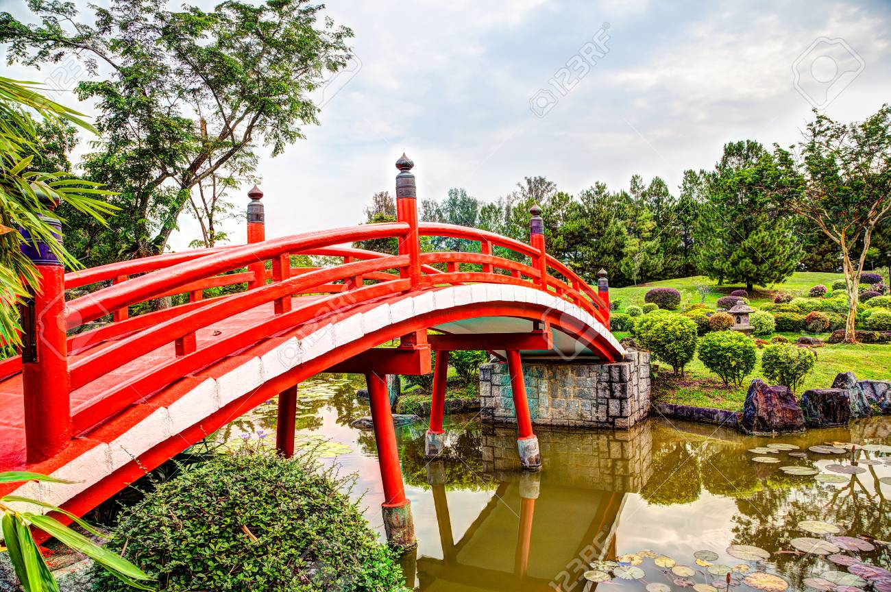 Red wooden bridge over tranquil pond at Japanese Garden, a free public park within Jurong Lake Gardens in Singapore. The gardens are popular among exercise enthusiasts, bird watchers and nature lovers. - 87708867