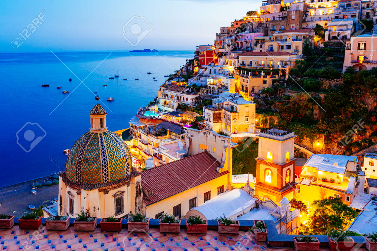 Positano, Amalfi Coast in Campania, Sorrento, Italy. View of the town and the seaside in a summer sunset - 76943152