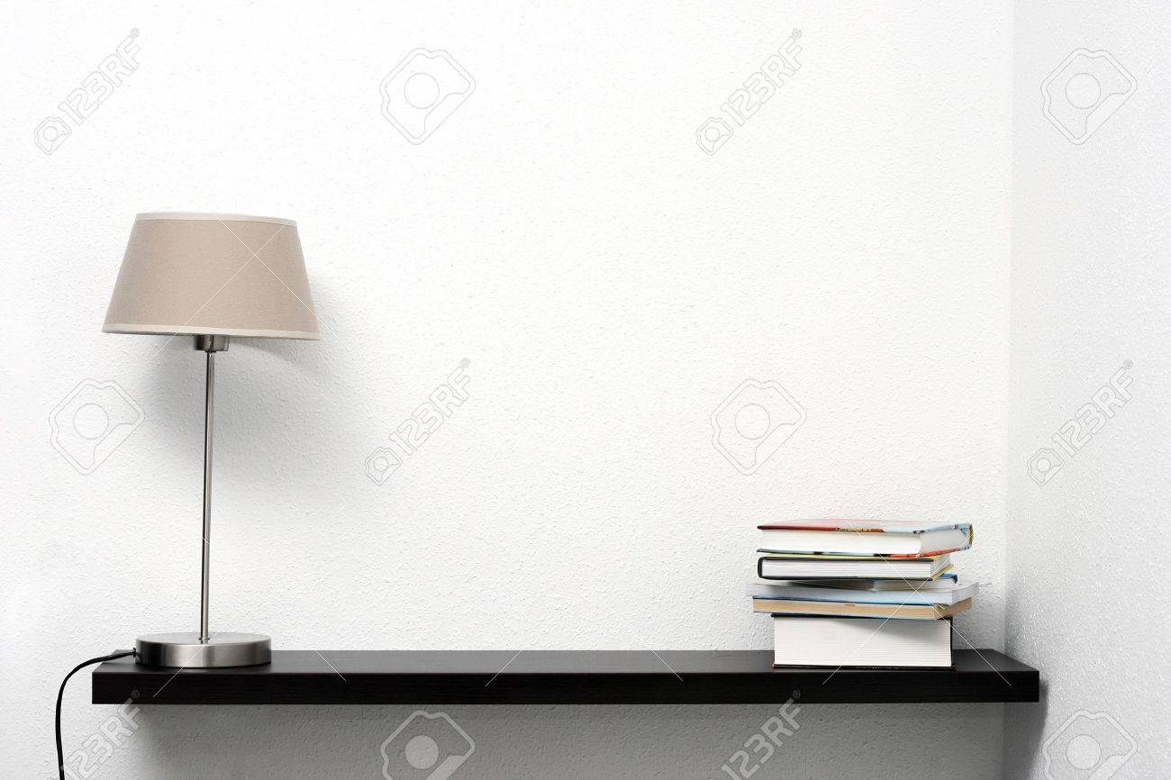 Bookshelf On The Wall With Lamp And Books Stock Photo