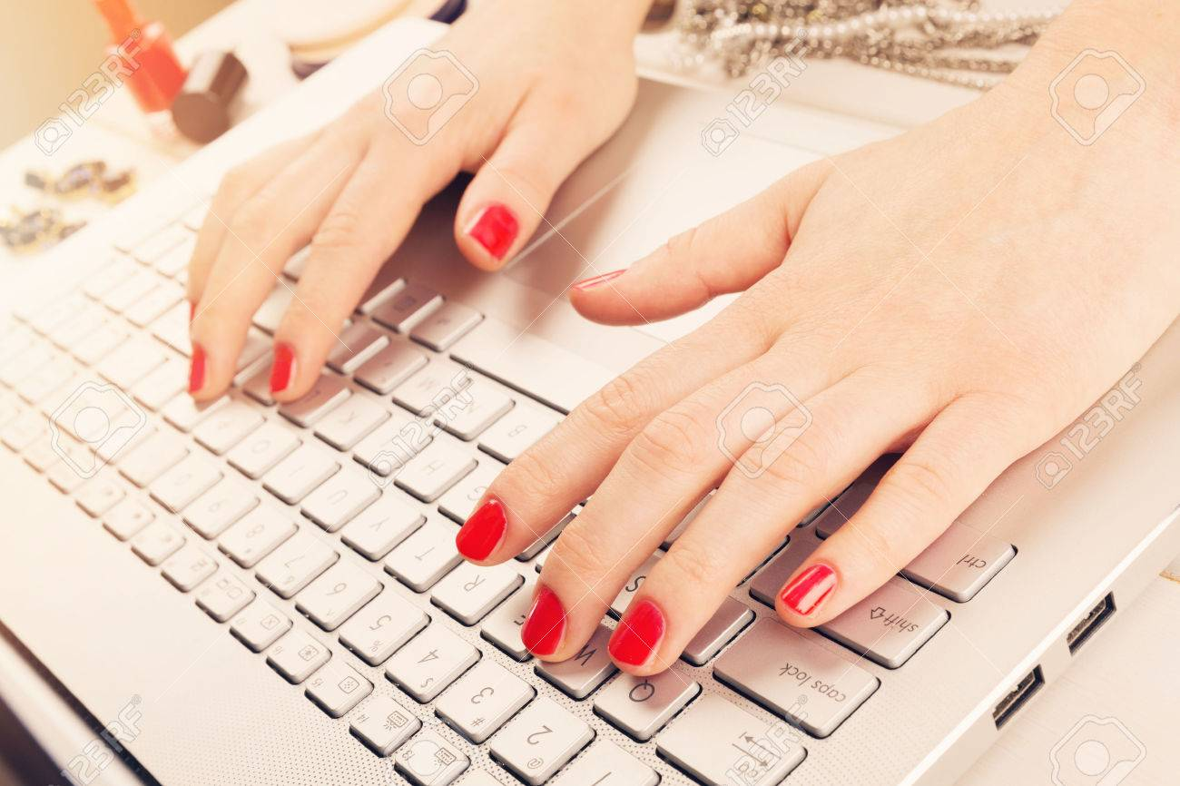 Fashion Woman With Red Polished Nails Working On Laptop Writing