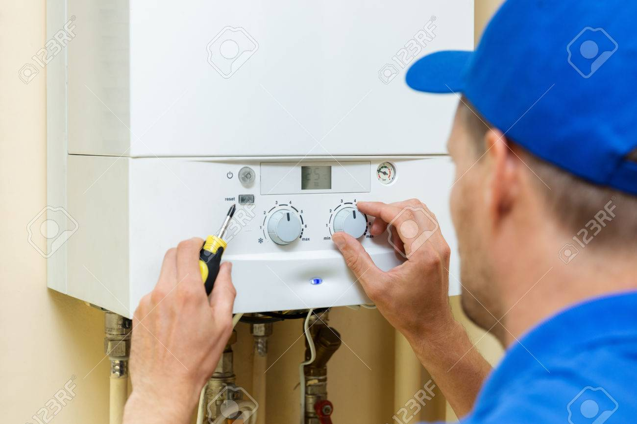 worker set up central gas heating boiler at home - 85023440
