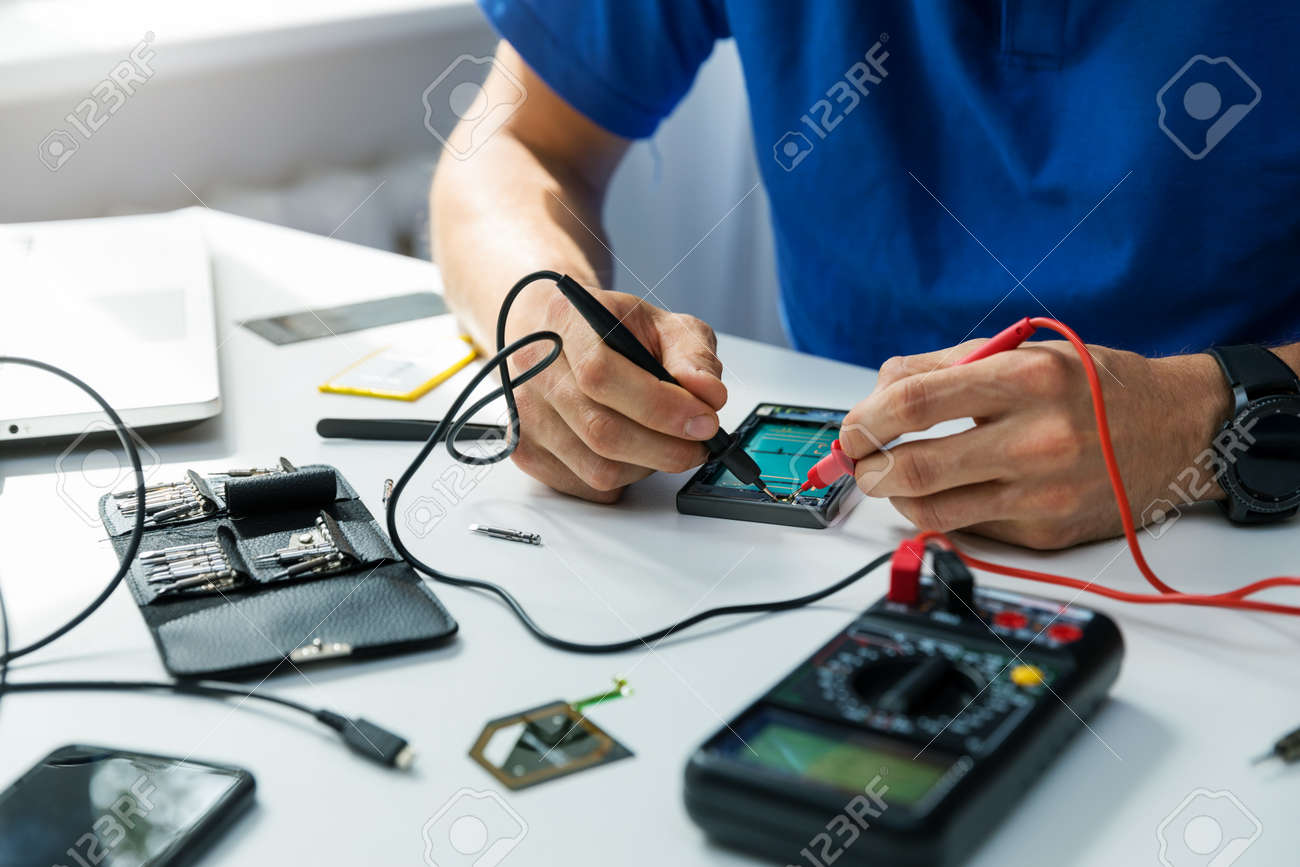 smartphone repair technician check the the phone with multimeter