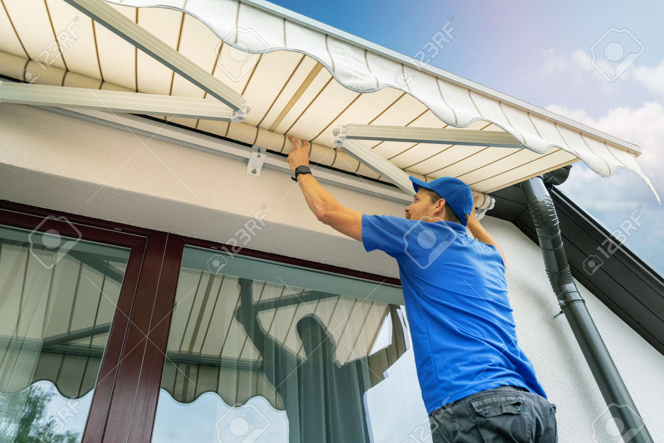 worker install an awning on the house wall over the terrace window - 110388561